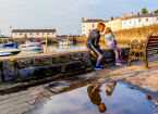 children sitting on a harbour wall