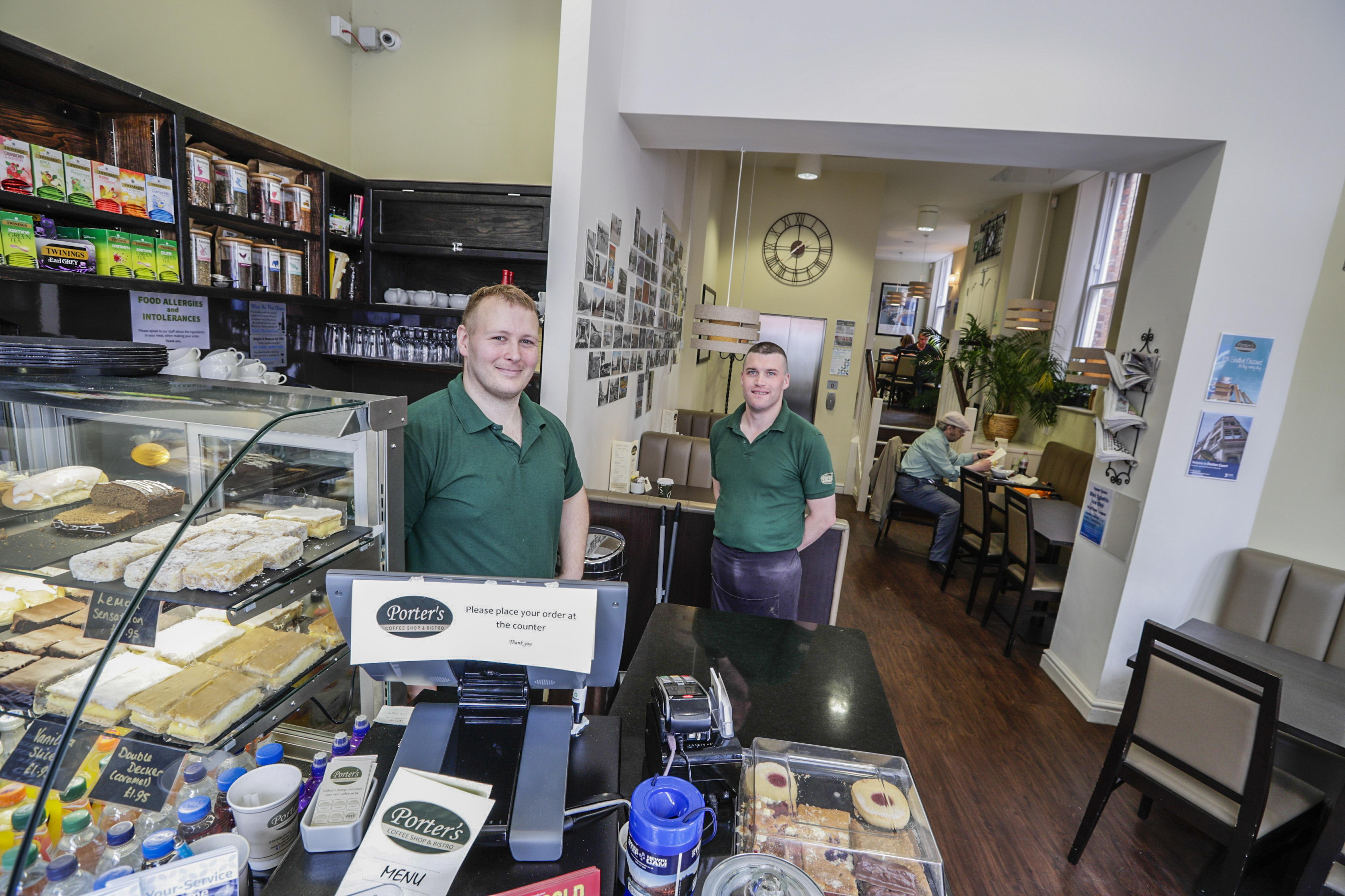 Two males behind counter at a Cafe