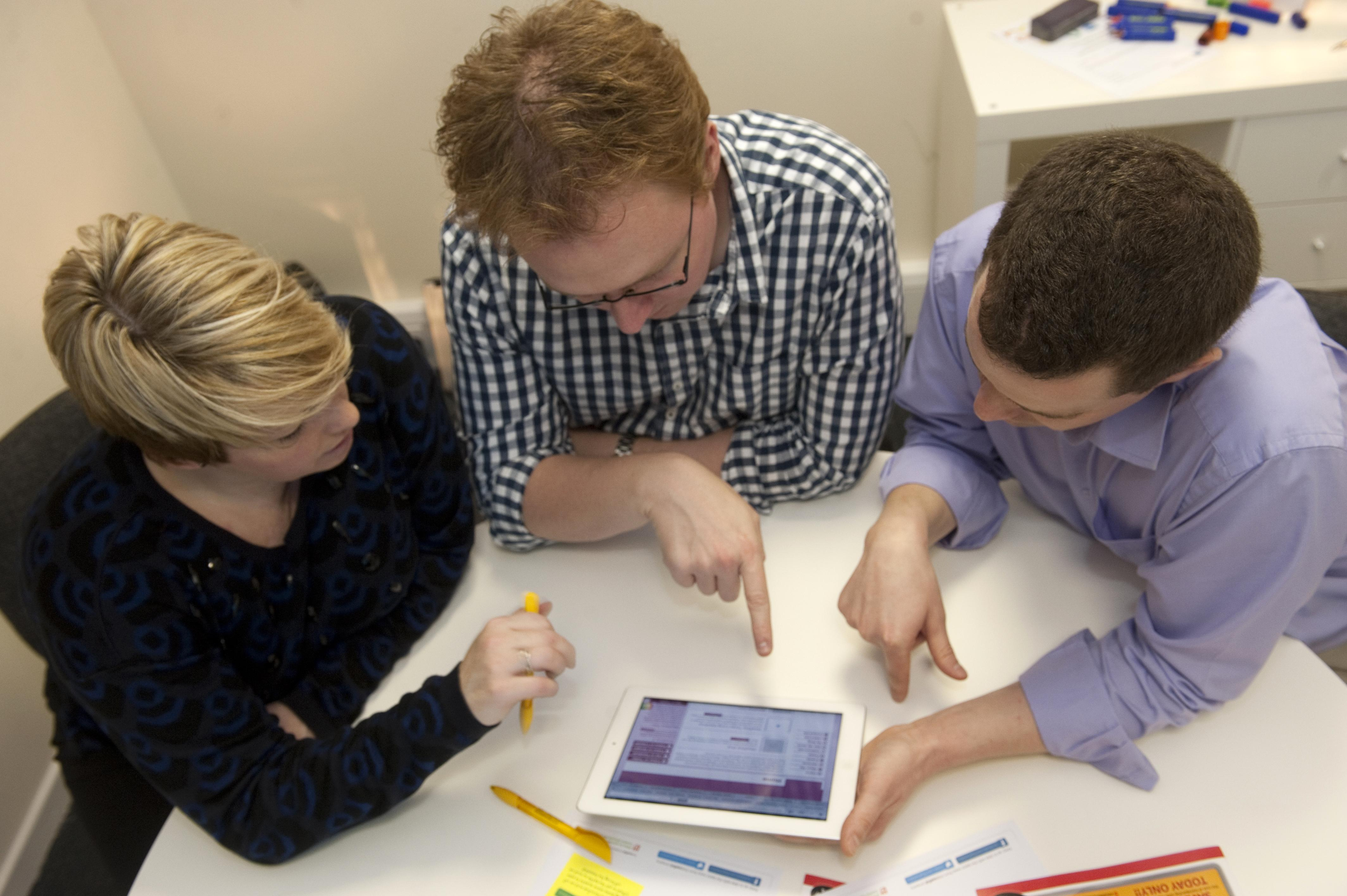 Three people using a tablet device