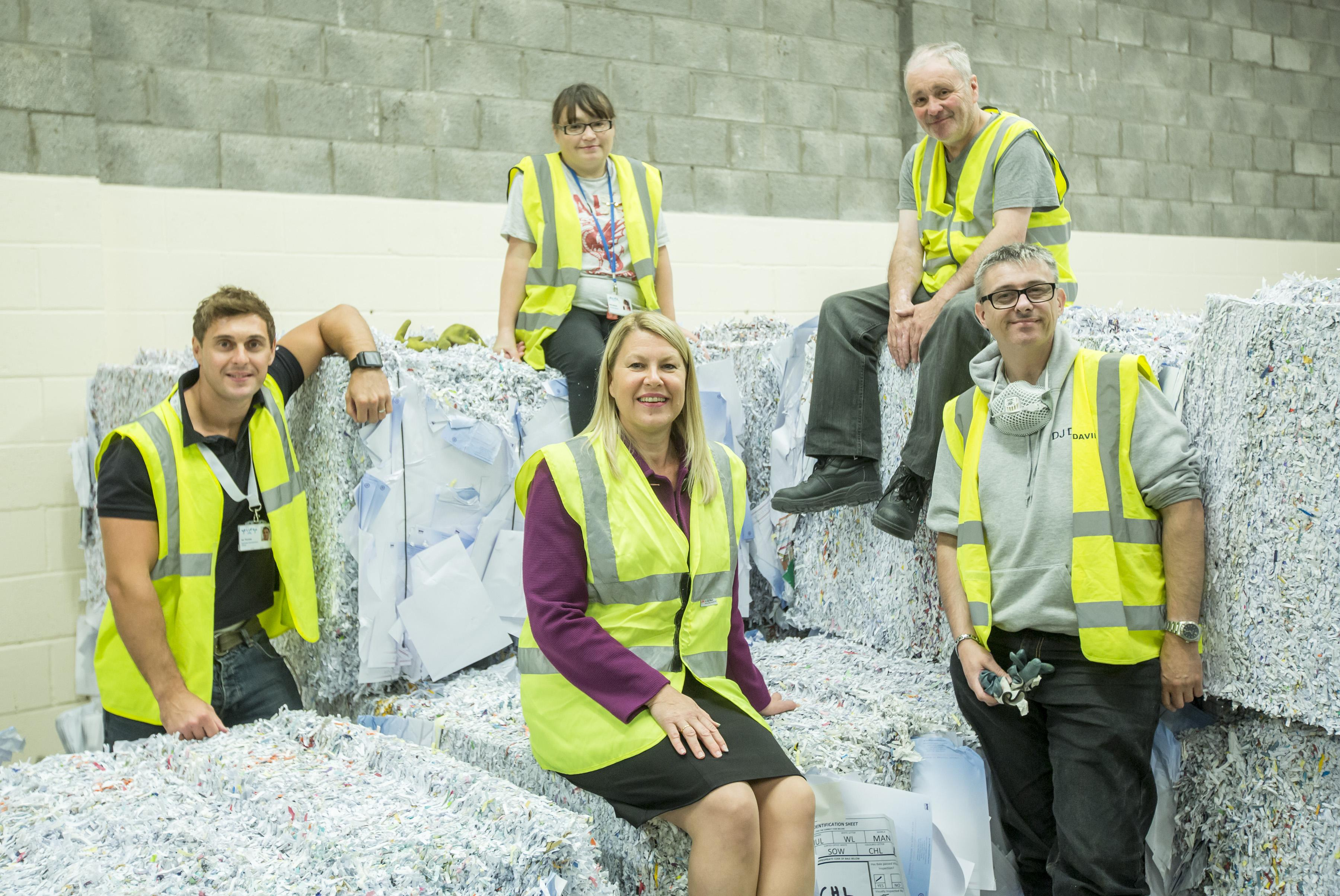 Staff in warehouse with bundled paper