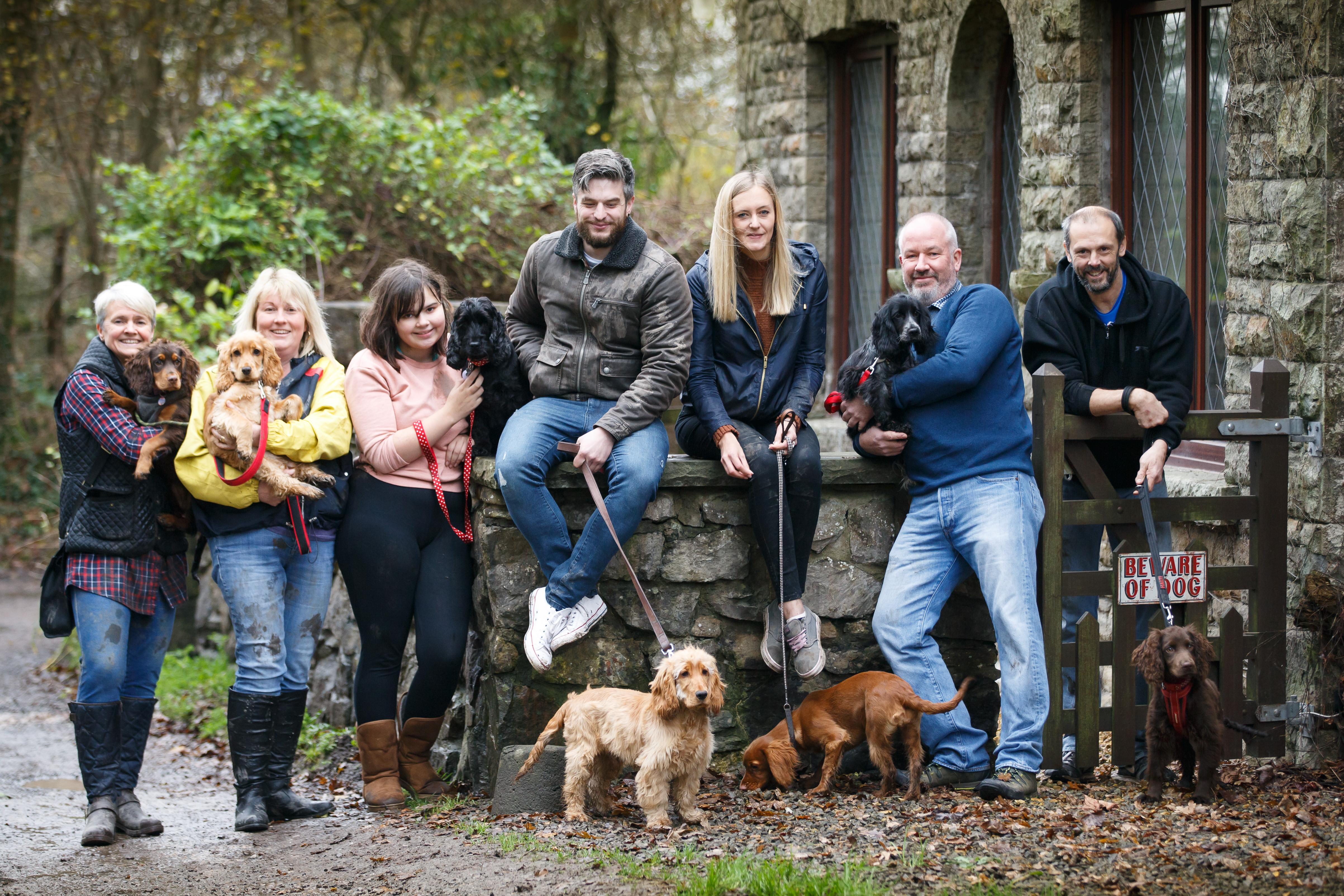 Group of dog walkers sat on wall