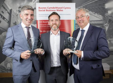Three men smiling with awards