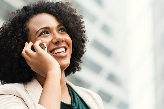A woman smiling and using a smartphone.