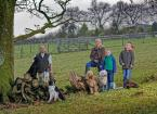 Family stand in field with dogs