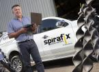 Spirafix employee stood by branded car and machinery