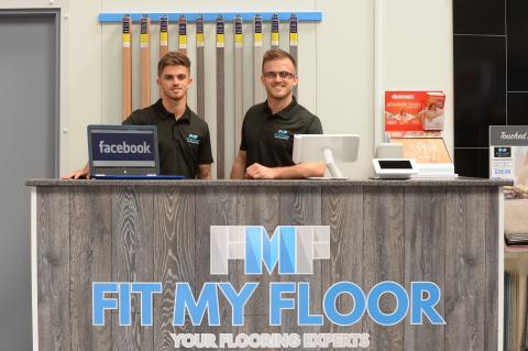 "2 men behind a ""Fit my floor"" counter"